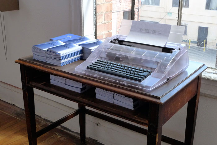 documentation photo of a desk with stacks of booklets and a typewriter on top of it