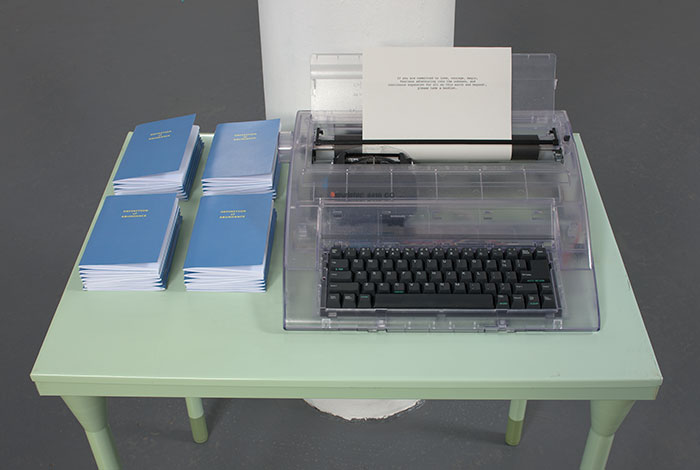 documentation photo of a green metal desk with stacks of booklets and a clear plastic typewriter on top of it and a note in the typewriter