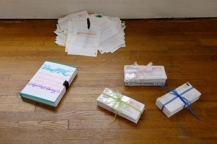 documentation photo of a handmade book, a pile of letters with a knife stabbed into it, and three bundles of letters tied with ribbon