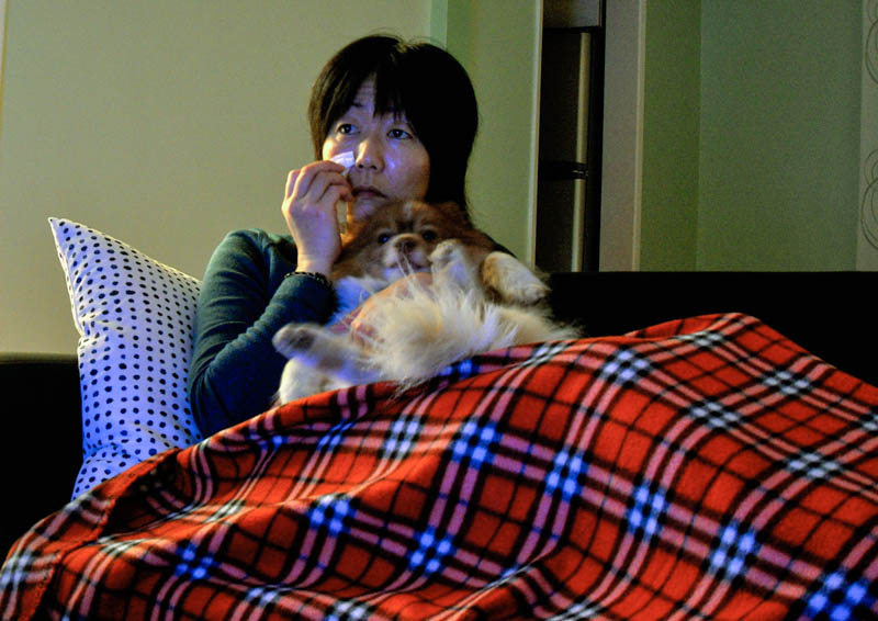 photo of Jennifer Moon sitting on the couch holding Mr. Snuggles and crying in the light of a TV