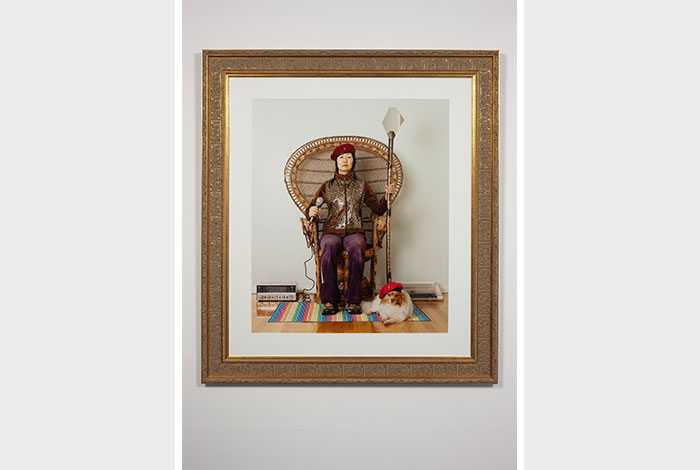 documentation photo of an ornately framed color photograph of Jennifer Moon wearing a beret sitting in a wicker chair holding a microphone in one hand and a staff in the other and a small dog wearing a beret at her feet