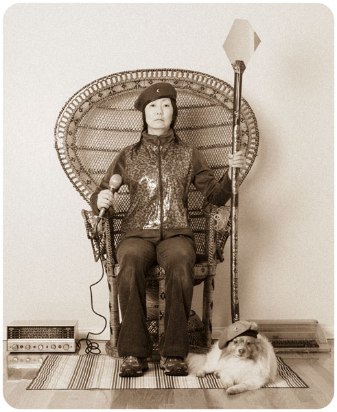 Remake of a famous Huey P. Newton photograph with Jennifer Moon wearing a beret sitting in a wicker chair holding a staff in one hand and a microphone in the other with Mr. Snuggles at her feet also wearing a beret