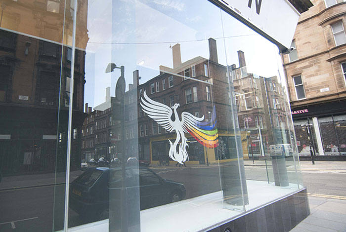 documentation photo detail of a window mural of a white phoenix with a rainbow trail from its left wing