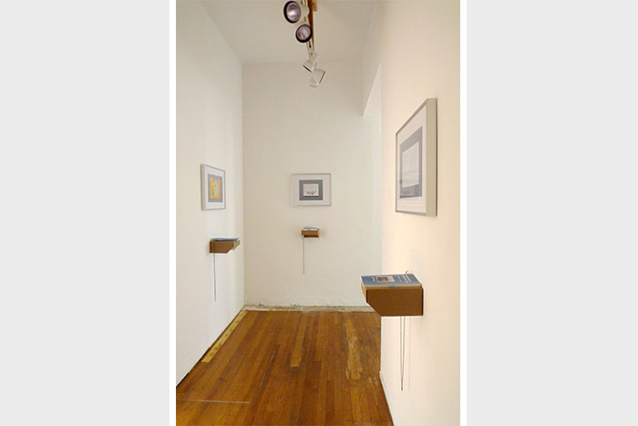 documentation photo of a narrow hallway containing three framed photographs and three books atop cardboard shelves underneath each framed photo