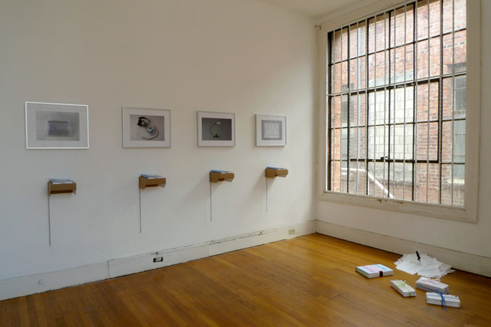 documentation photo of a room containing four framed photographs and four books atop cardboard shelves underneath each framed photo and sculptural objects on the floor