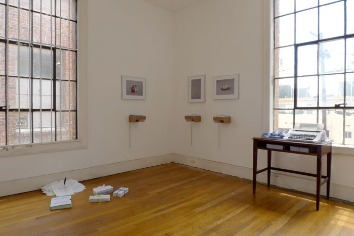 documentation photo of a room containing sculptural objects on the floor, three framed photographs with three books atop cardboard shelves underndeath each photo, and a desk containing stacks of booklets and a typewriter