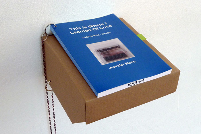 documentation photo of a book on a cardboard shelf with a chain attaching the book to the shelf