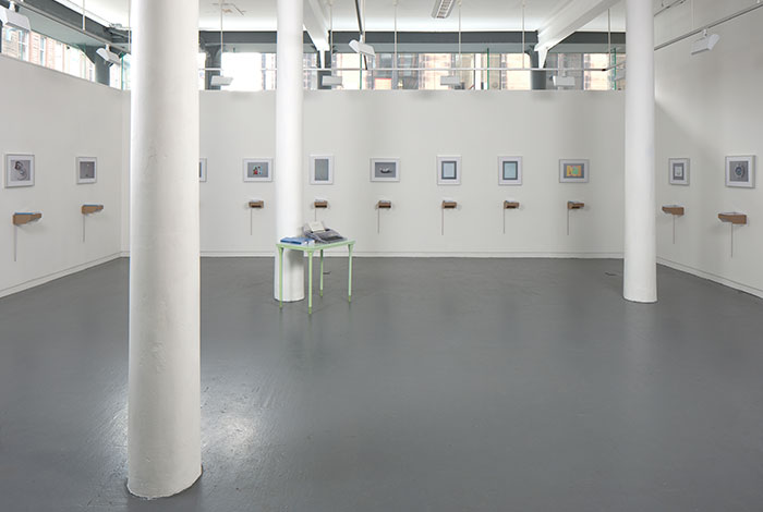 documentation photo of a large room with three pillars containing eleven framed photographs and eleven books atop cardboard shelves underneath each framed photograph and a green metal desk with a clear plastic typewriter and stacks of booklets on top of it