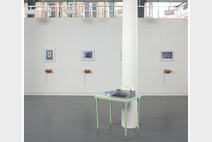 documentation photo of a wall with four hung, framed photographs and four books atop cardboard shelves underneath each framed photograph and a pillar in front of the wall with a green metal desk next to it holding a clear plastic typewriter and stacks of booklets