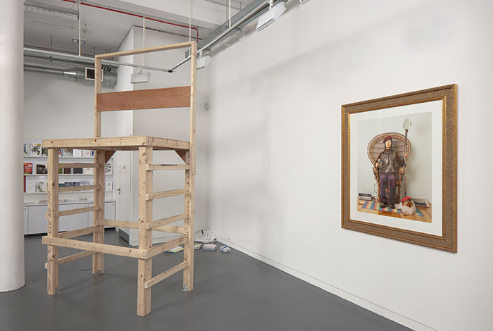 documentation photo of a large wooden platform, sculptural objects on the floor behind the platform, and a large framed photograph hung on a wall
