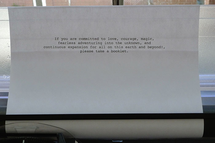 documentation photo of a note in a typewriter that reads, If you are committed to love, courage, magic,         fearless adventuring into the unknown, and         continuous expansion for all on this earth and beyond!,         please take a booklet.